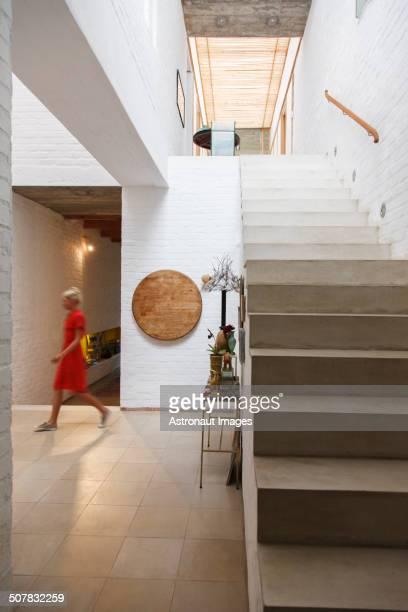 Woman walking by doorway in modern house