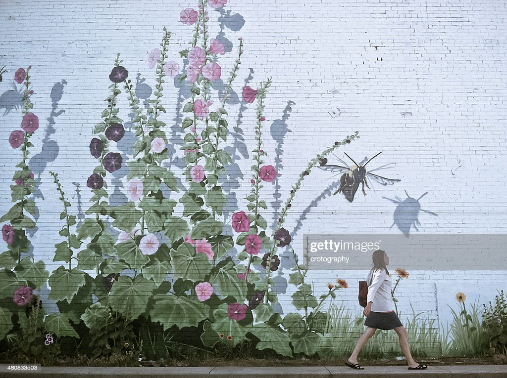 Woman walking by flowery wall : Stock Photo