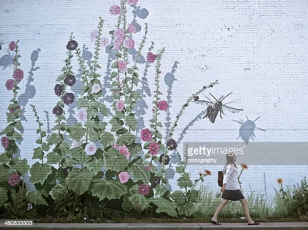 Woman walking by flowery wall