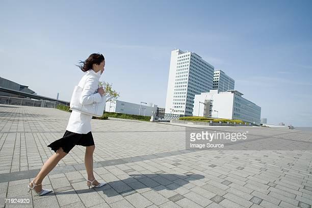 女性を歩くオフィスビル