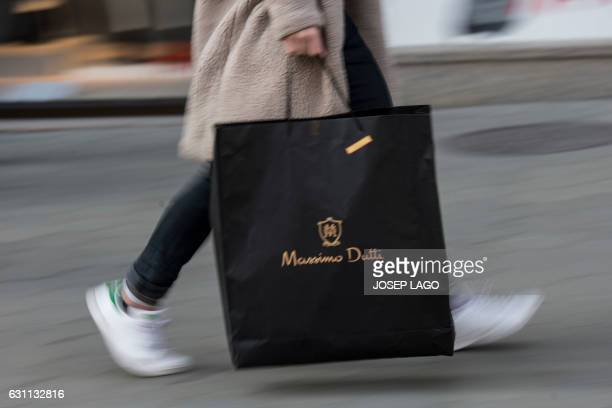 A woman walking carries a Massimo Dutti shopping bag on the first day of the winter sales in Barcelona on January 7 2017 / AFP PHOTO / Josep LAGO