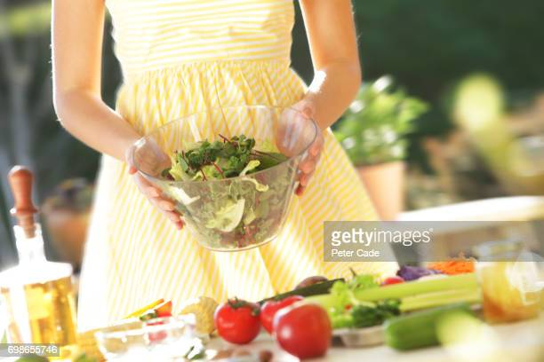 Woman walking carrying bowl of salad leaves towards table in summer