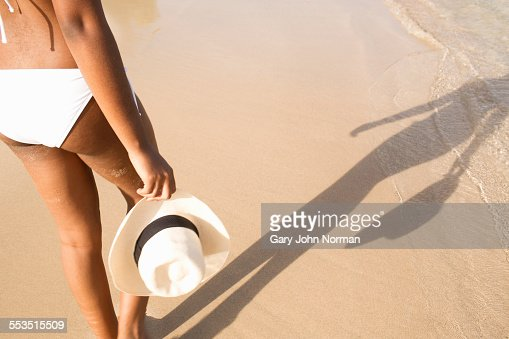 Woman walking close to shoreline on beach.