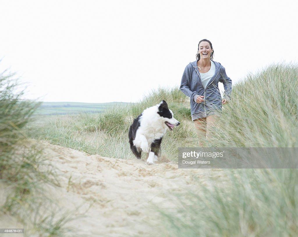 Woman walking dog at beach. : Stock Photo