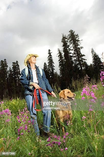 Woman walking dog in field
