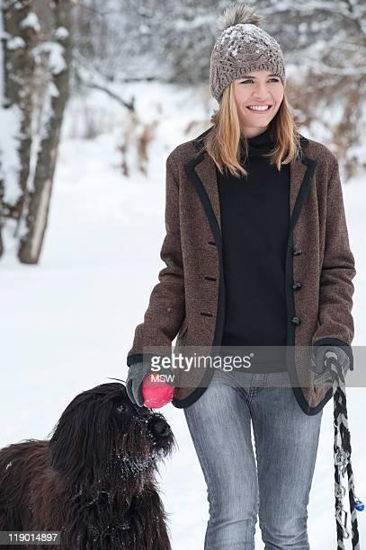 Mujer caminar Perro en la nieve