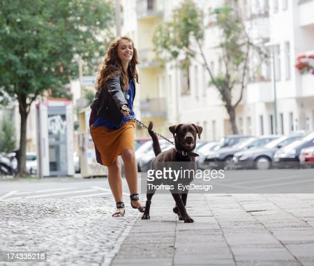 Woman Walking Dog on a City Street