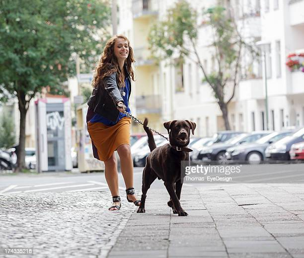 Woman Walking Dog on a City Street