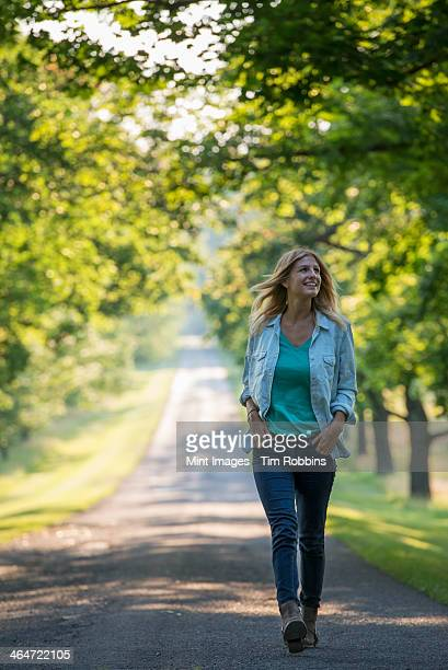 A woman walking down a tree lined path.