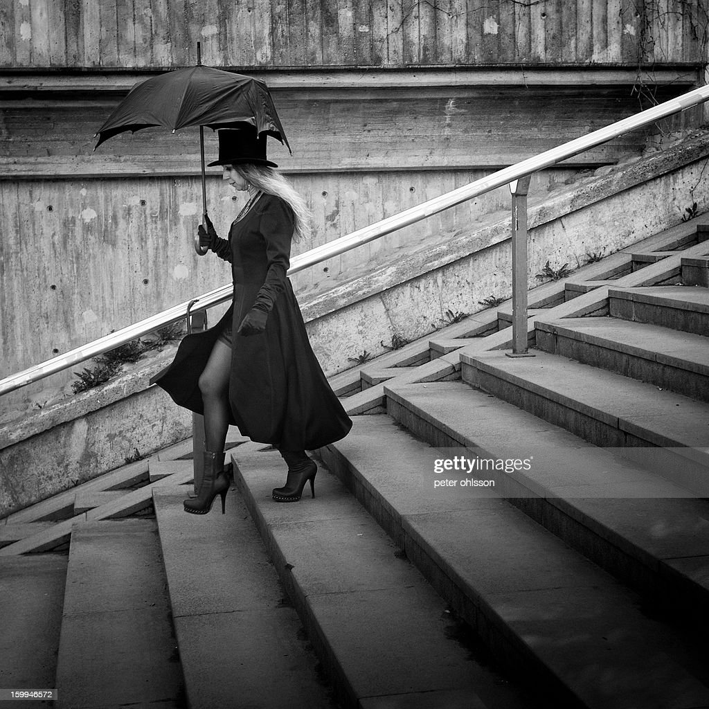 CONTENT] Woman walking down concrete stairs with a broken umbrella and a top hat.