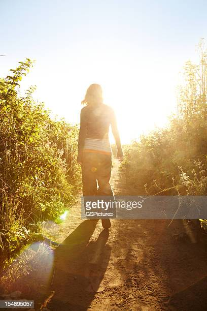 Woman walking down pathway in nature