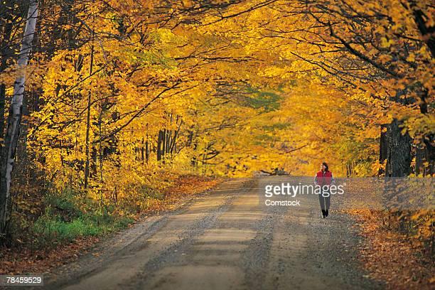 Woman walking down rural road in autumn