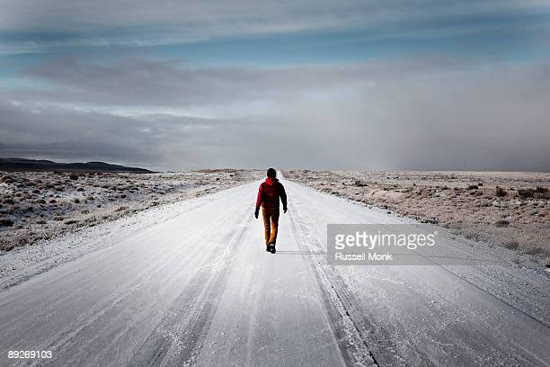 Woman walking down snowy deserted road