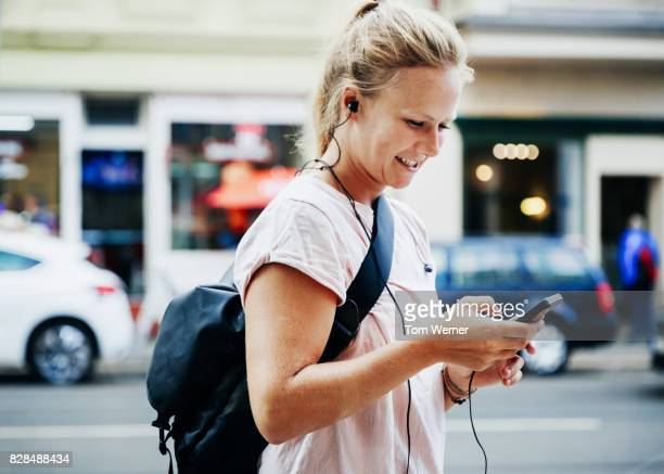 Woman Walking Down Street listening To Music On Smartphone