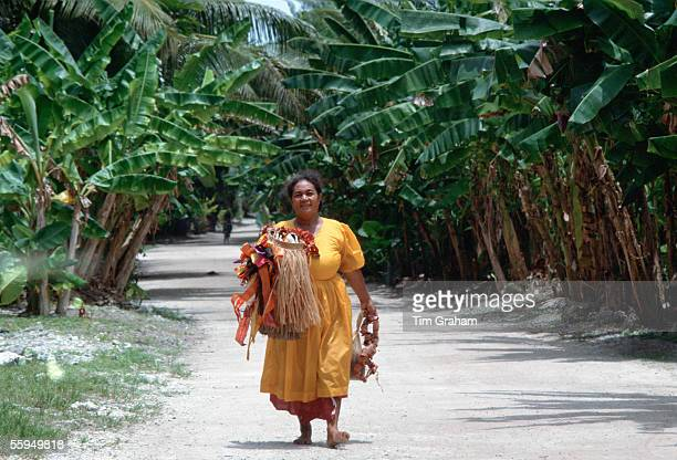 Woman walking down the main street of Tuvalu South Pacific