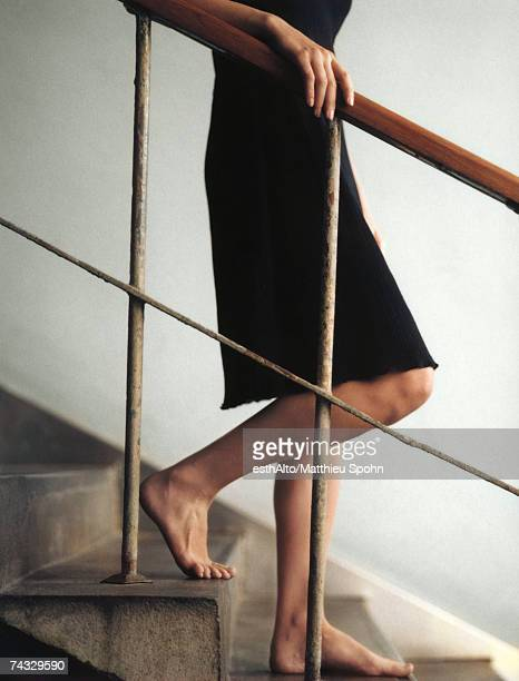 Woman walking downstairs barefoot, chest down