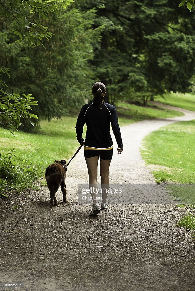 Woman walking her dog in the park  : Stock Photo