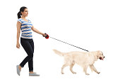 Full length profile shot of woman walking her dog isolated on white background