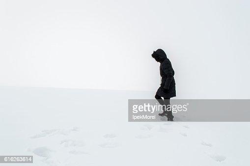 Woman walking in a snowy field : Stock Photo