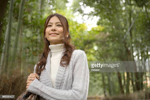 Woman walking in bamboo forest, smiling