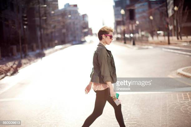 Woman walking in city intersection