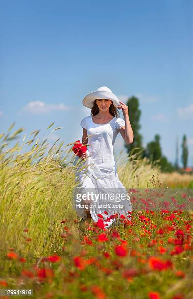 Woman walking in field of flowers