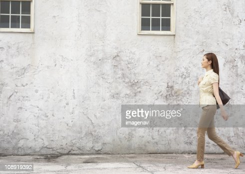 Woman walking in front of wall
