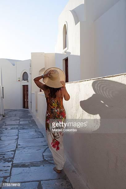 Woman walking in greek village street in Santorini