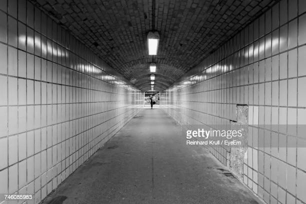 Woman Walking In Illuminated Tunnel