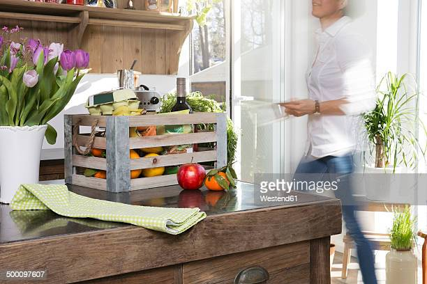 Woman walking in kitchen with crate of groceries on counter