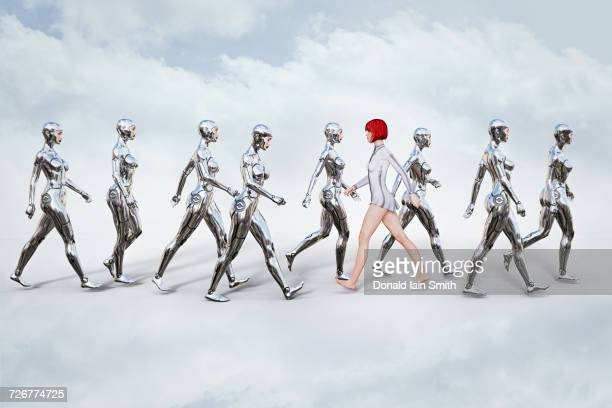 Woman walking in opposite direction of robots