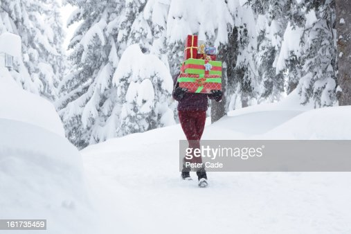 Woman walking in snow carrying presents