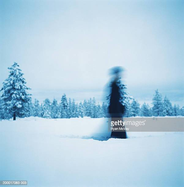 Woman walking in snow (blurred motion)