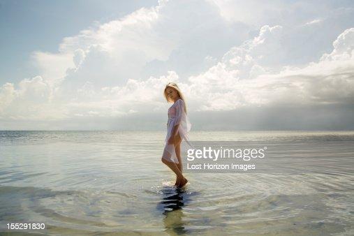 Woman walking in still ocean water