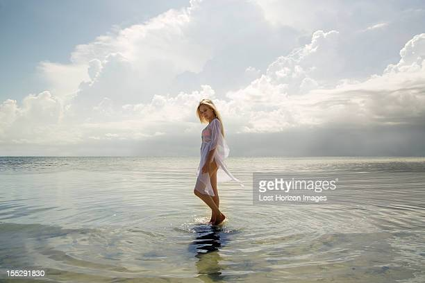 Woman walking in still ocean water