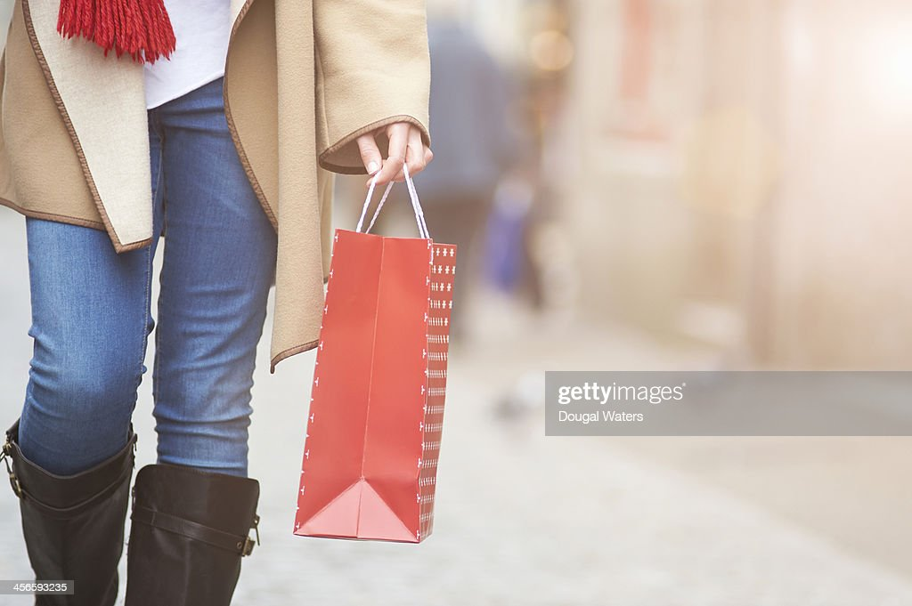 Woman walking in street with gift bag, close up.