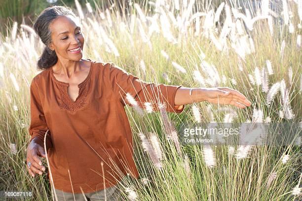 Frau zu Fuß in einem sonnigen Feld
