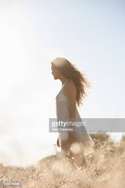 Woman walking in tall grass