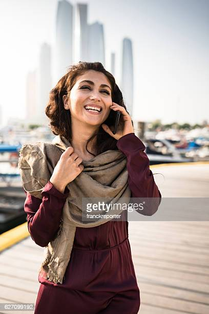 woman walking in the abu dhabi marina on the phone