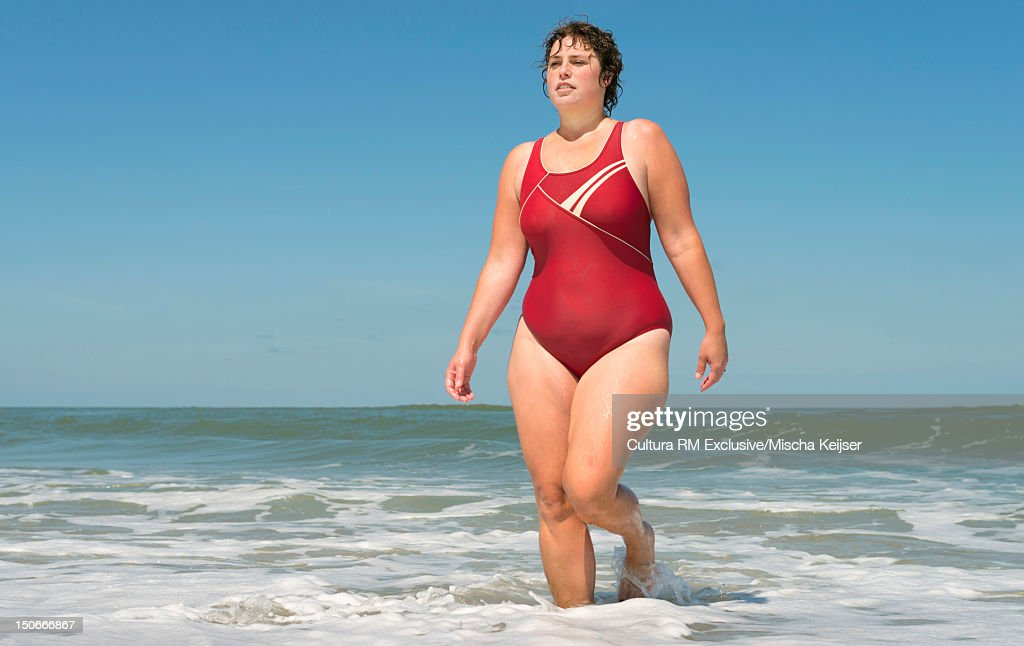 Woman walking in water on beach : Stock Photo