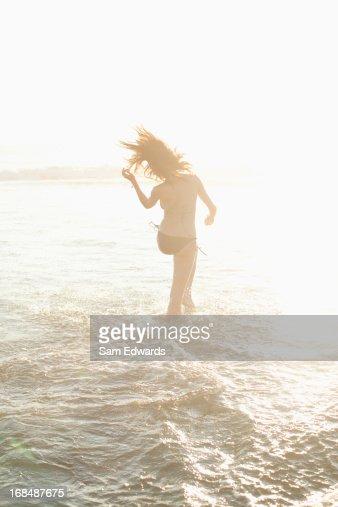 Woman walking in waves on beach : Stock Photo