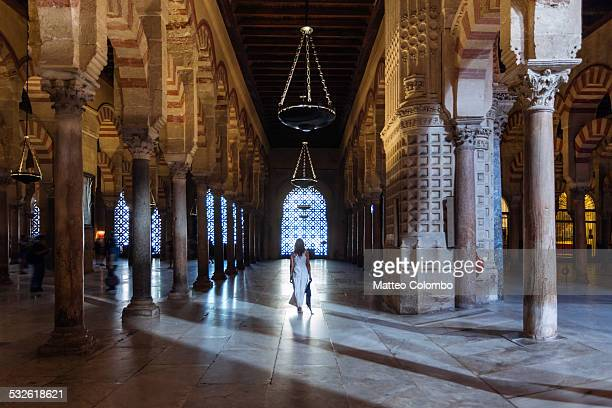 Woman walking inside the Mezquita, Cordoba, Spain