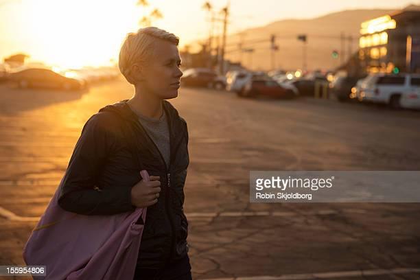 Woman walking n sunset with bag over shoulder
