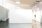 Woman walking near blank white wall mockup in modern gallery. Girl admires a clear big stand mock up in museum with contemporary art exhibitions. Large hall interior, banner exposition show