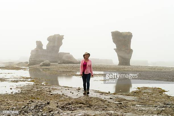 Woman walking near monoliths, morning fog