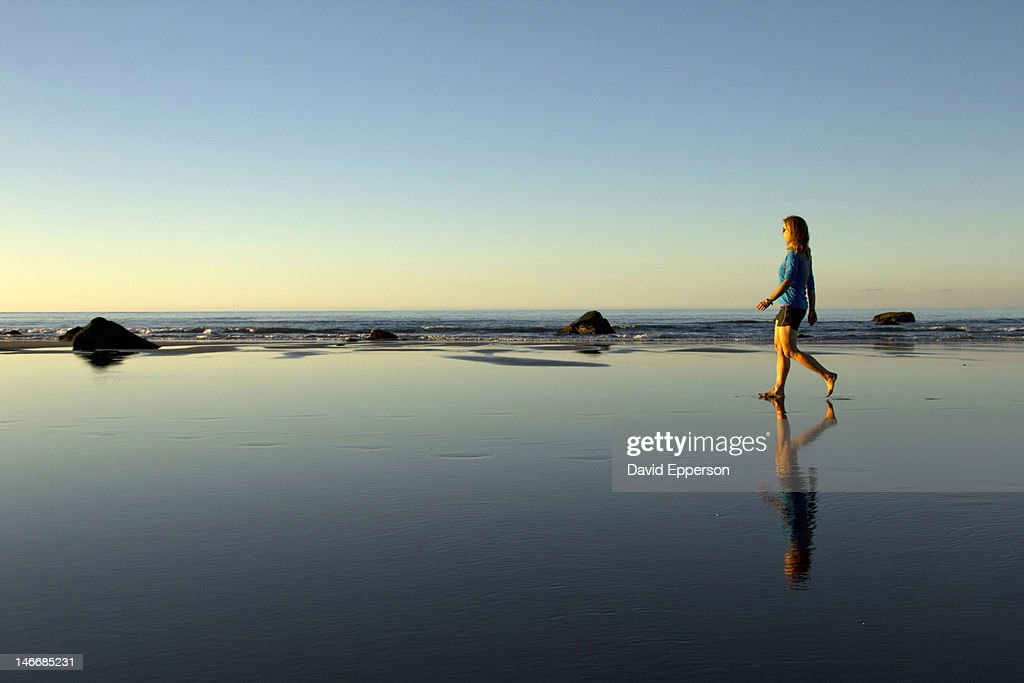 A woman walking on a beach at sunset