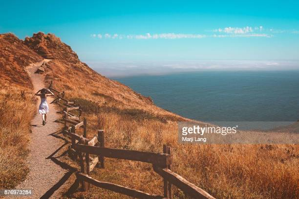 Woman walking on a coastline footpath by the Pacific ocean at Point Reyes National Seashore USA