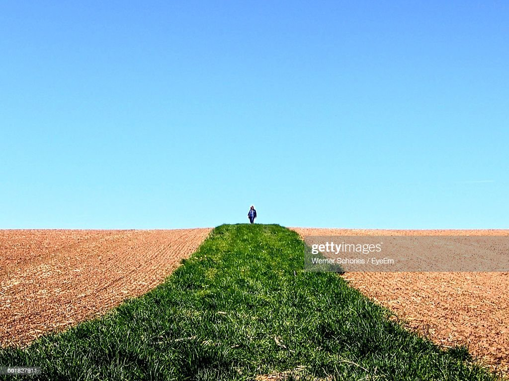 Woman Walking On Agricultural Field Against Clear Blue Sky