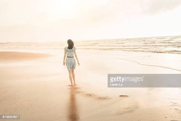 Woman walking on beach alone