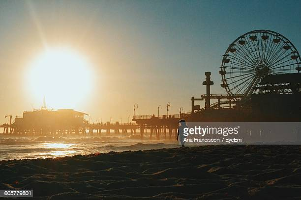 Woman Walking On Beach By Santa Monica Pier Against Clear Sky During Sunset